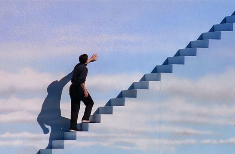 Uomo sale delle scale dipinte di azzurro come il cielo