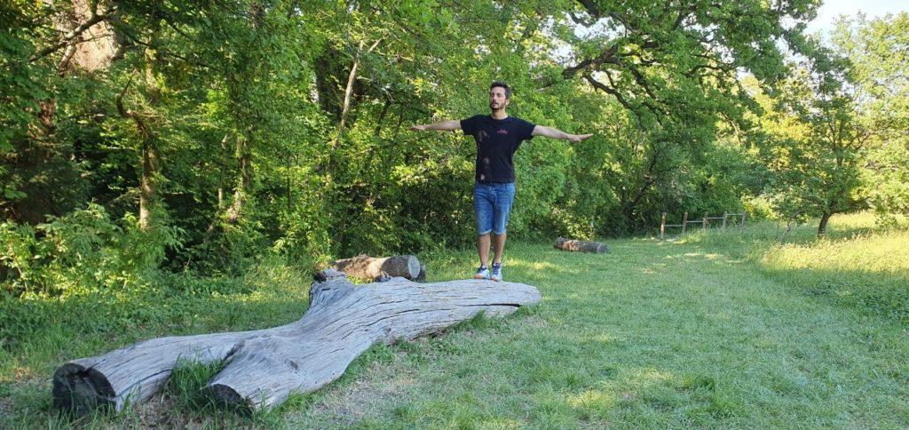 Attore cammina su un tronco d'albero