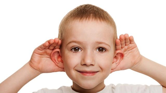 Bambino che mette le mani alle orecchie per ascoltare